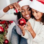 Mom and young daughter decorating Christmas tree
