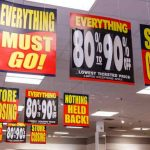 liquidations and store closing signs hanging in retail space